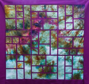 Framed quilt top made with hand-dyed feature fabric